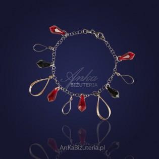 Srebrna bransoletka z kryształami Swarovski i elementami złoconymi.